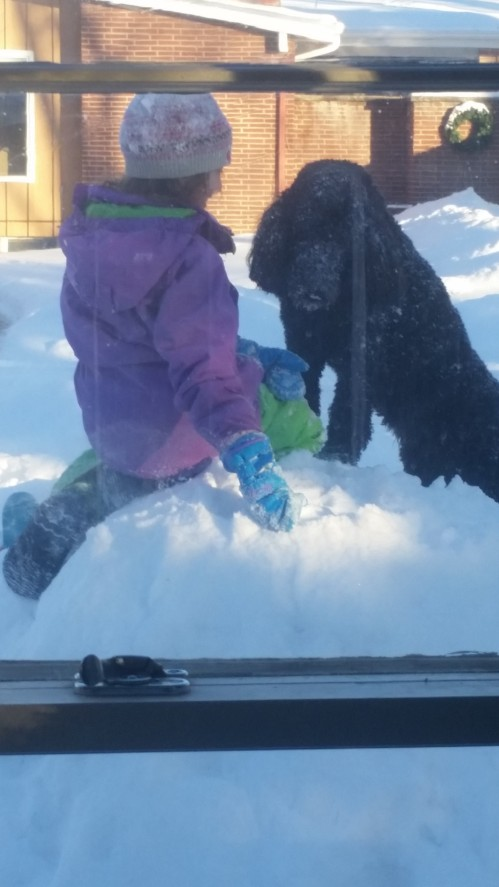 Sophie loves the snow, she is playing with one of the girls.